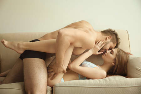 Photo pour Sexy young couple in underwear lying on sofa at home - image libre de droit