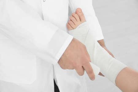 Photo pour Doctor applying bandage onto patient's leg in clinic, closeup - image libre de droit