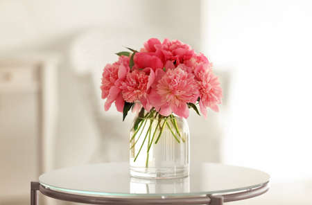 Photo for Glass vase with beautiful peonies on table - Royalty Free Image