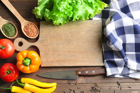 Foto de Wooden board with vegetables on kitchen table. Cooking classes concept - Imagen libre de derechos