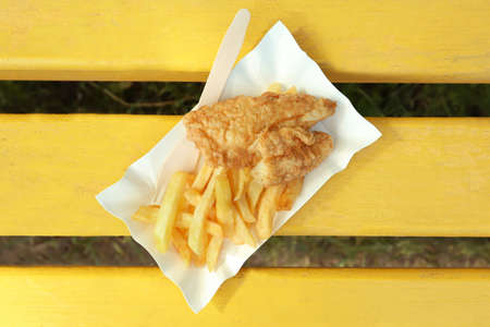 Photo for Tasty fried fish and chips on wooden bench - Royalty Free Image