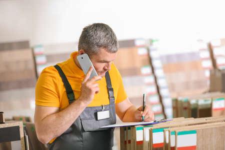 Foto für Carpenter talking on phone in hardware store - Lizenzfreies Bild