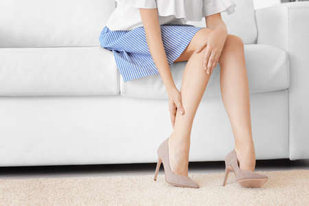 Photo pour Young woman suffering from leg pain at home - image libre de droit