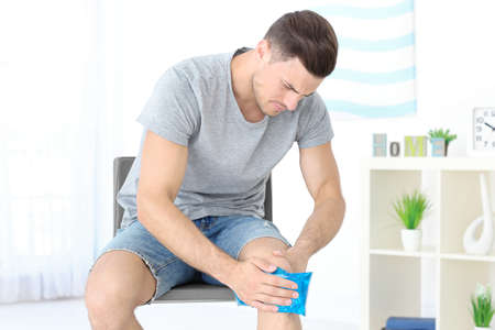 Photo pour Young man applying cold compress to leg at home - image libre de droit