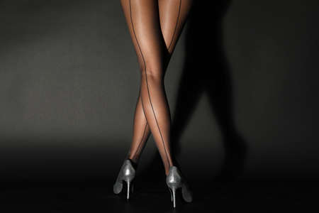 Photo for Legs of beautiful young woman in tights on dark background - Royalty Free Image