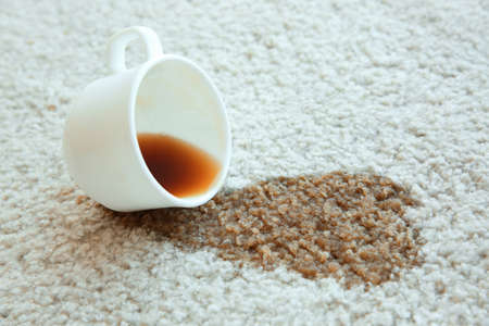Photo pour Cup of coffee spilled on white carpet, close up - image libre de droit