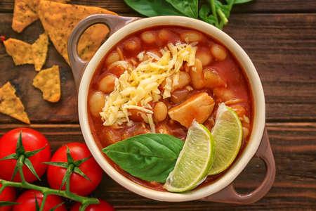 Photo pour Composition with delicious turkey chili in casserole on wooden table - image libre de droit