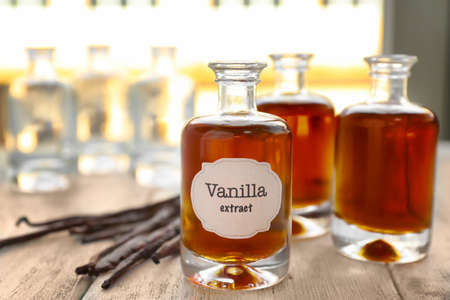 Photo for Bottles with aromatic extract and dry vanilla beans on table - Royalty Free Image