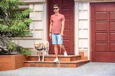 Photo pour Guide dog helping young blind man outdoors - image libre de droit