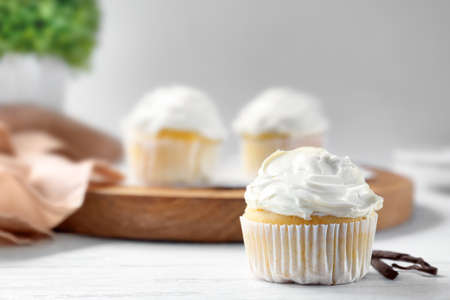 Photo for Tasty vanilla cupcake on wooden table - Royalty Free Image
