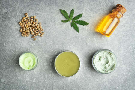 Photo pour Composition with hemp cosmetic products and natural ingredients on grey background - image libre de droit