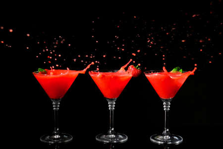 Foto de Glasses of delicious strawberry daiquiri with splash on black background - Imagen libre de derechos