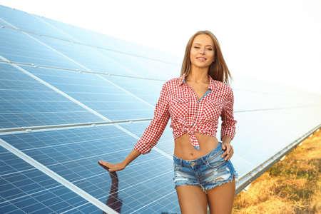 Foto de Beautiful young woman near solar panels outdoors - Imagen libre de derechos