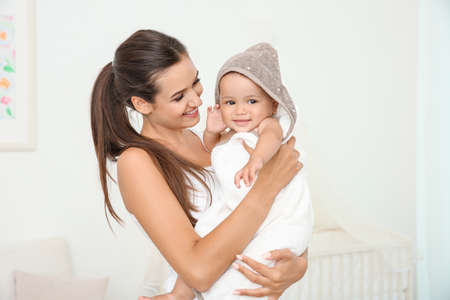 Foto de Mother holding cute baby in towel after bathing at home - Imagen libre de derechos