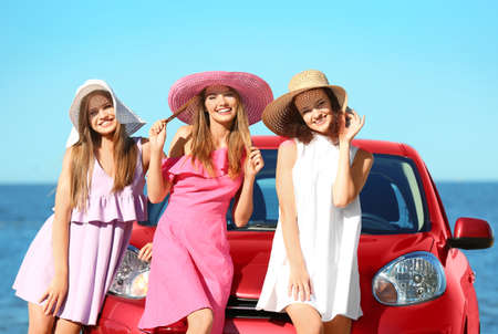 Photo for Beautiful young women near car at sea resort - Royalty Free Image
