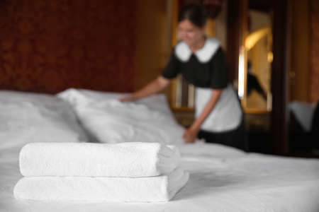 Photo for Clean white towels on bed in hotel room and blurred chambermaid on background - Royalty Free Image