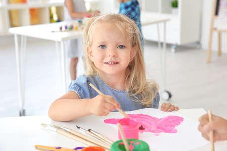 Foto de Little girl at painting lesson in classroom - Imagen libre de derechos