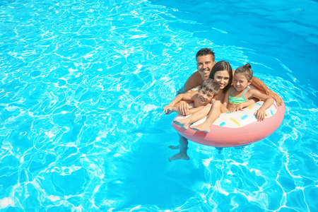 Photo for Happy family with inflatable ring relaxing in swimming pool - Royalty Free Image