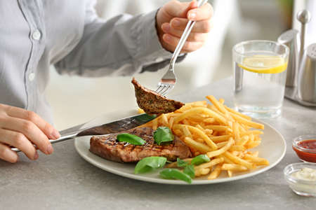 Foto de Woman eating delicious grilled steak with fries in restaurant - Imagen libre de derechos