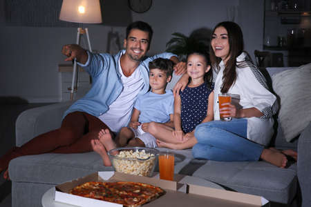 Photo pour Happy family watching TV on sofa at night - image libre de droit