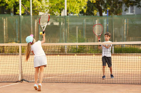 Photo for Cute little children playing tennis on court - Royalty Free Image