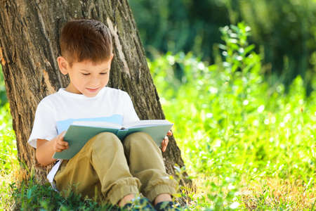 Photo pour Cute little boy reading book in park - image libre de droit