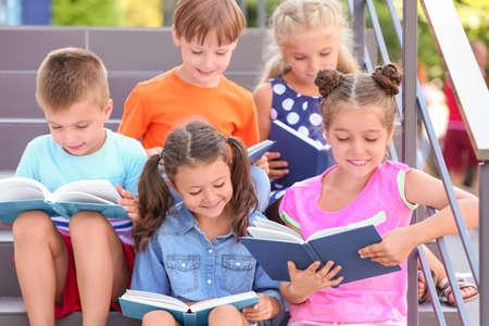 Foto de Cute little children reading books while sitting on steps outdoors - Imagen libre de derechos