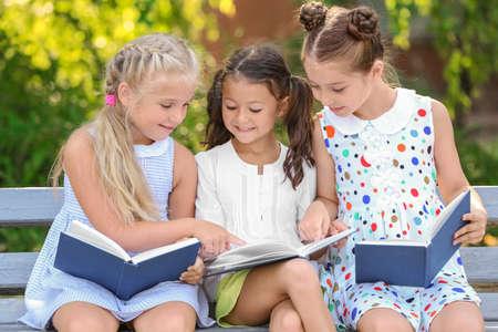 Foto de Cute little children reading books in park - Imagen libre de derechos