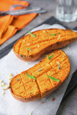 Photo for Cutting board with baked sweet potato on table - Royalty Free Image