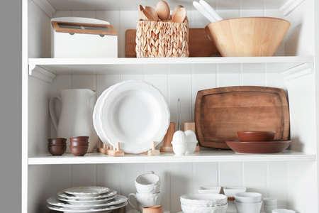 Foto de Storage stand with tableware and kitchen utensils indoors - Imagen libre de derechos