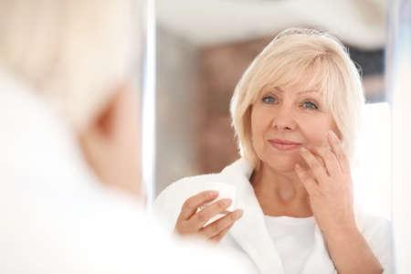 Photo pour Mature woman applying anti-aging cream at home - image libre de droit