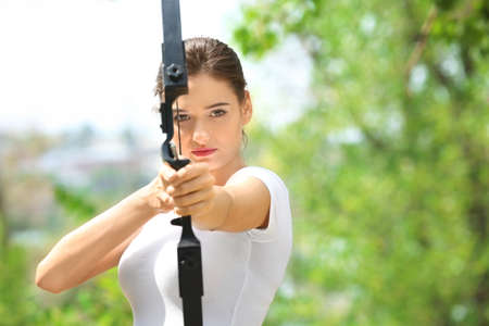 Photo for Young woman practicing archery outdoors - Royalty Free Image