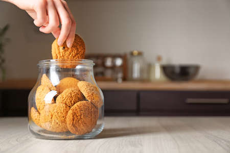 Foto de Woman taking oatmeal cookie from glass jar - Imagen libre de derechos