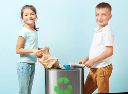 Photo for Little children throwing garbage into litter bin on color background. Recycling concept - Royalty Free Image