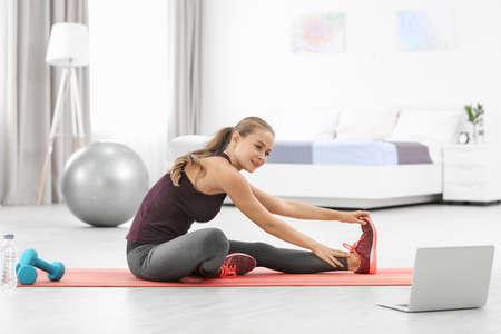Foto de Young sporty woman with laptop practicing yoga at home - Imagen libre de derechos