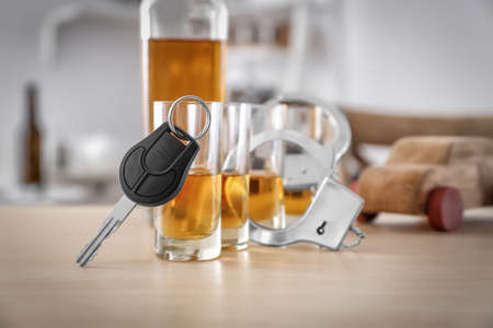 Foto de Glasses of alcohol with handcuffs and car key on wooden table. Don't drink and drive concept - Imagen libre de derechos