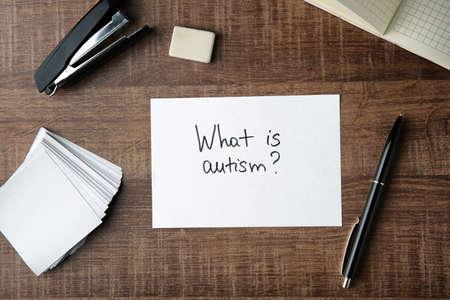 Foto de Paper with text WHAT IS AUTISM? and stationery on wooden background - Imagen libre de derechos