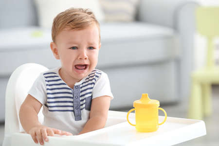 Photo pour Adorable crying baby sitting in highchair at home - image libre de droit