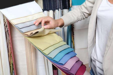 Foto de Young woman choosing fabric for new curtains in shop - Imagen libre de derechos
