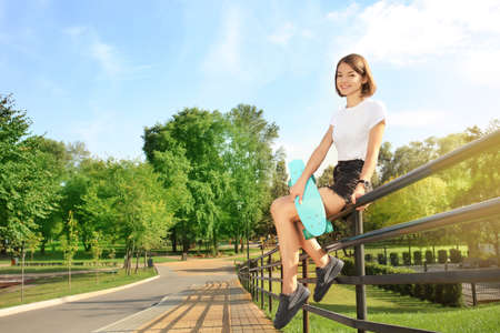 Photo pour Hipster girl with skateboard sitting on fence in park - image libre de droit
