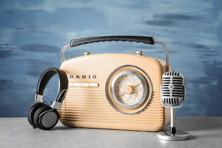 Foto de Retro radio, microphone and headphones on table against blue wall - Imagen libre de derechos