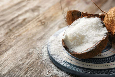 Photo for Desiccated coconut in nut on wooden table - Royalty Free Image