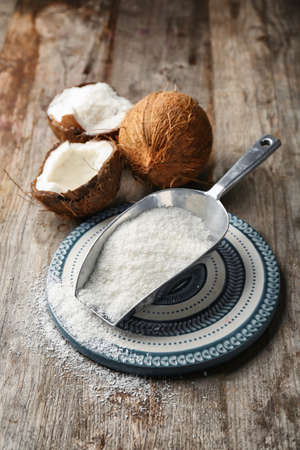 Photo for Desiccated coconut in scoop on wooden table - Royalty Free Image