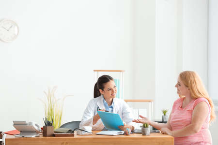 Photo pour Young female doctor consulting overweight woman in clinic - image libre de droit