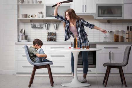 Foto de Drunk woman threatening her son in kitchen - Imagen libre de derechos