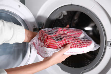 Photo pour Woman putting mesh with red sneakers into washing machine, closeup - image libre de droit