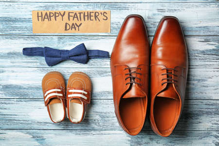 Photo pour Bow tie, big and small shoes on wooden background. Father's day composition - image libre de droit
