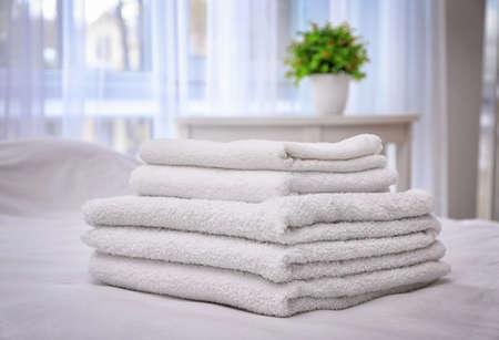 Foto de White bath towels on bed in hotel suite - Imagen libre de derechos
