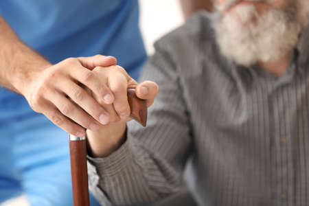 Photo for Senior man and young caregiver holding hands on walking stick, closeup - Royalty Free Image