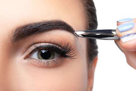 Photo pour Young woman correcting eyebrow shape, closeup - image libre de droit